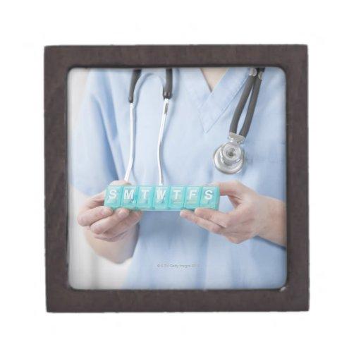 Female doctor holding pill box, mid section premium keepsake boxes