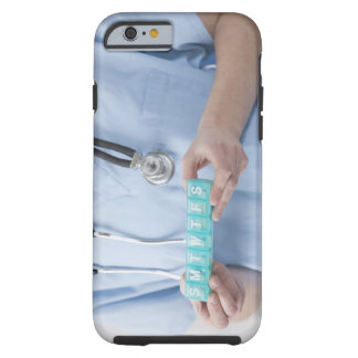 Female doctor holding pill box, mid section tough iPhone 6 case