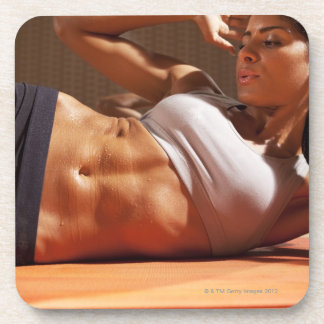 Female doing intense crunches, beverage coaster