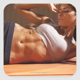 Female doing intense crunches, square sticker