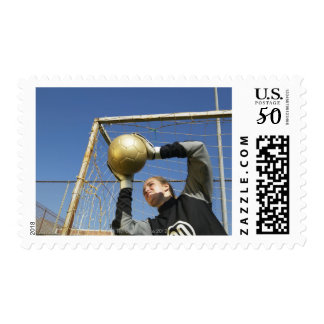 Female goalie (12-14) holding ball, low angle postage