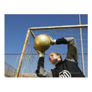 Female goalie (12-14) holding ball, low angle postcard