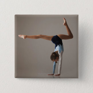 Female gymnast (12-13) performing handstand button