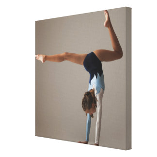 Female gymnast (12-13) performing handstand canvas print