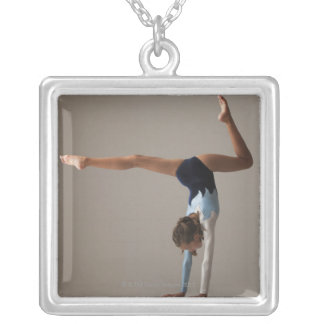 Female gymnast (12-13) performing handstand silver plated necklace