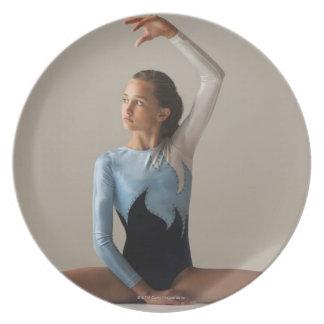 Female gymnast (12-13) performing splits dinner plate