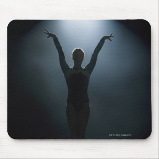 Female gymnast performing in spotlight, studio mouse pad