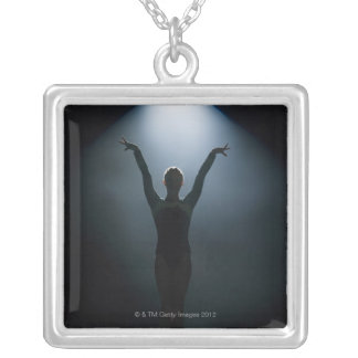 Female gymnast performing in spotlight, studio silver plated necklace