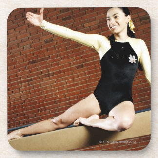 Female gymnast practicing on a balance beam and drink coaster