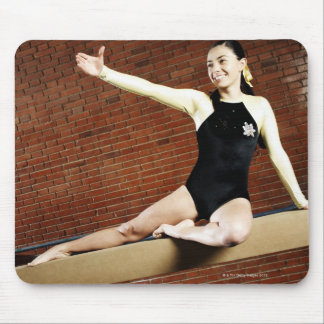 Female gymnast practicing on a balance beam and mouse pad