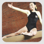 Female gymnast practicing on a balance beam and square stickers