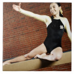 Female gymnast practicing on a balance beam and ceramic tiles