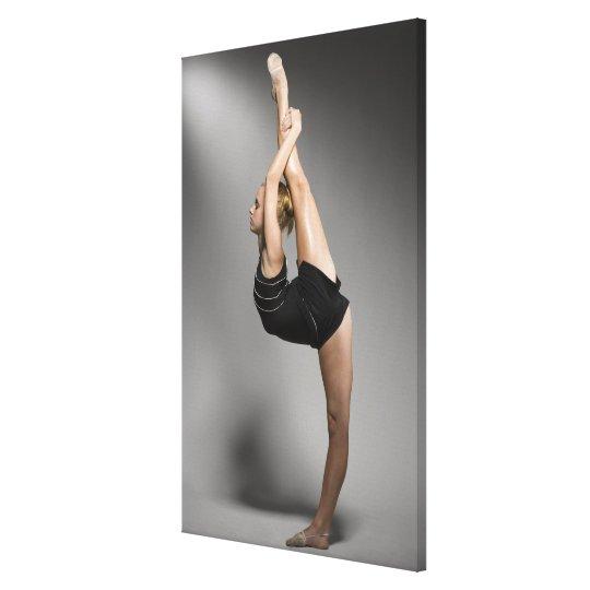 Female gymnast stretching, studio shot canvas print