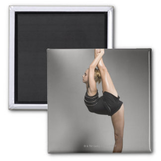 Female gymnast stretching, studio shot magnet