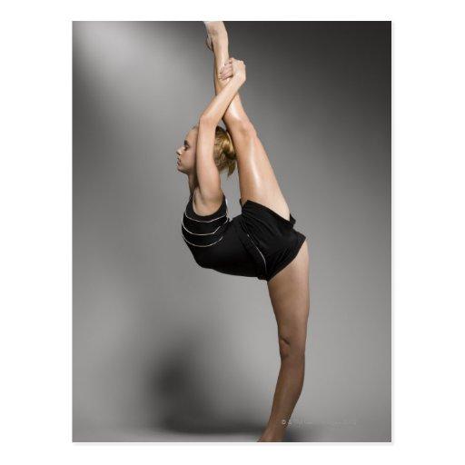 Female gymnast stretching, studio shot postcard