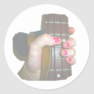 female hand holding four string bass neck faded round stickers
