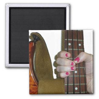 female hand holding four string bass neck fridge magnets