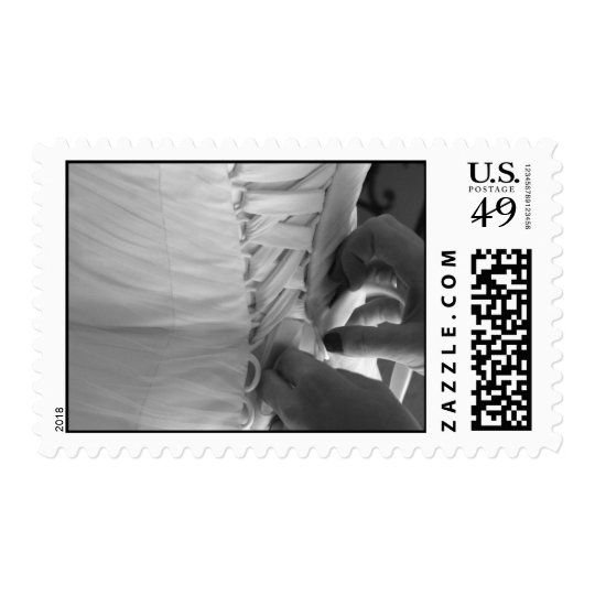 Female hand lacing up wedding dress back postage