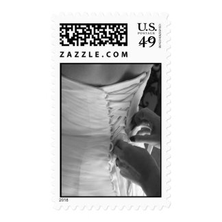 Female hand lacing up wedding dress back postage stamp