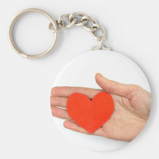 Female hand showing red paper heart as symbol keychain