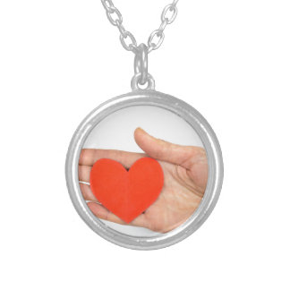 Female hand showing red paper heart as symbol round pendant necklace
