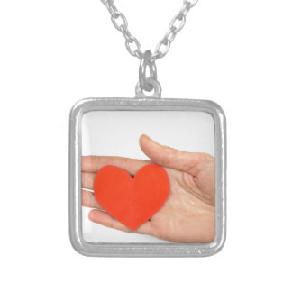 Female hand showing red paper heart as symbol square pendant necklace