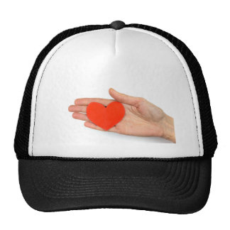 Female hand showing red paper heart as symbol trucker hat