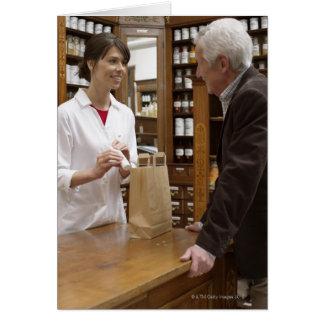 Female pharmacist advising customers card