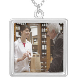 Female pharmacist advising customers silver plated necklace