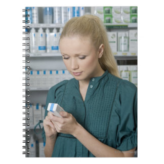 Female pharmacist looking at medicine in 2 notebook