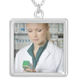 Female pharmacist looking at medicine in silver plated necklace