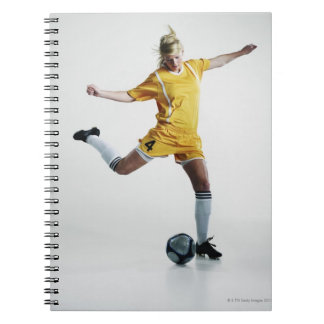 Female soccer player preparing to kick soccer notebook