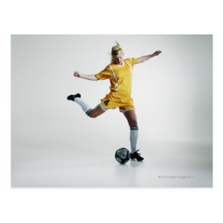 Female soccer player preparing to kick soccer post card