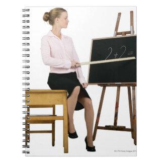 Female Teacher Pointing Ruler at Chalkboard Notebook