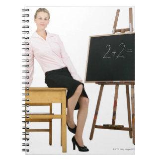 Female Teacher Posing by Wooden Desk Spiral Notebook