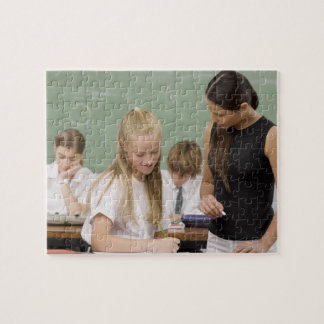 Female teacher teaching a schoolgirl with other jigsaw puzzle