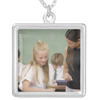 Female teacher teaching a schoolgirl with other silver plated necklace