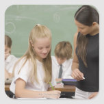 Female teacher teaching a schoolgirl with other stickers