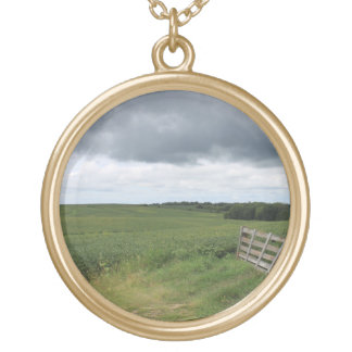 fence gate in front of field with mowed horseshoe gold plated necklace