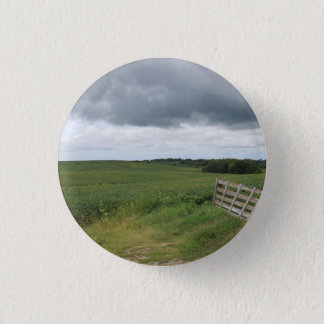 fence gate in front of field with mowed horseshoe pinback button
