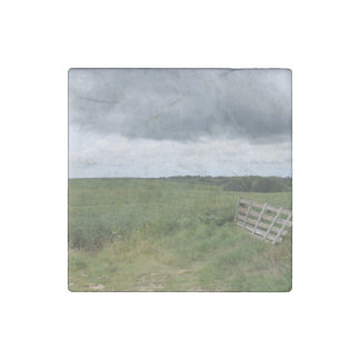 fence gate in front of field with mowed horseshoe stone magnet