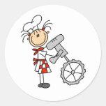 Figura cocinero del palillo que usa a los etiqueta redonda