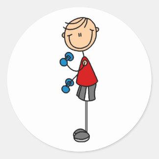 Figura del palillo del muchacho que ejercita al pegatina redonda