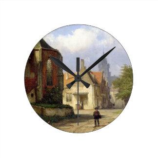 Figure antes de una iglesia de ladrillo en una ciu reloj redondo mediano