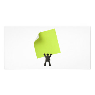 Figurine holding a piece of blank yellow paper photo card template