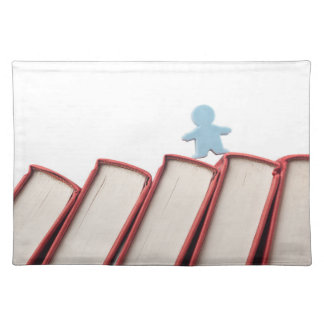 Figurine on the spine of books place mats