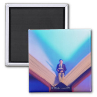 Figurine sitting on open book 2 inch square magnet