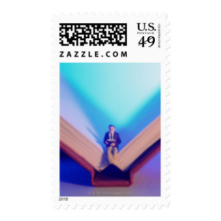 Figurine sitting on open book postage
