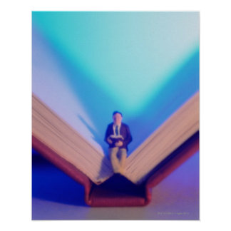 Figurine sitting on open book poster