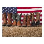 Fila de las botas de vaquero en haystack postal